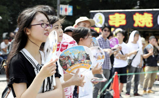 最高気温が39.9度を記録した名古屋市内で、うちわを使って涼を求める人たち(5日)=共同
