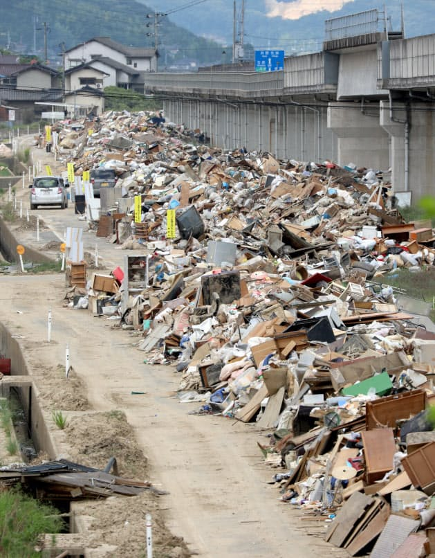 道路に積み上げられた大量の災害廃棄物。岡山県全体で約41万トンと推計され、県の年間ごみ総排出量の6割に相当する(1日、岡山県倉敷市真備町地区)