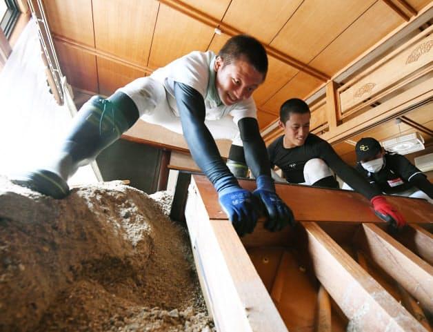 ボランティアに参加し、家財道具を運び出す高校球児。2年生の浦早秀君(16)は「家が土砂に埋まっていて信じられない光景だった。作業はしんどいけど、被災者の方はもっとつらい思いをしている。そう考えると頑張れる」と手に力を込めた(7月31日、広島県坂町)