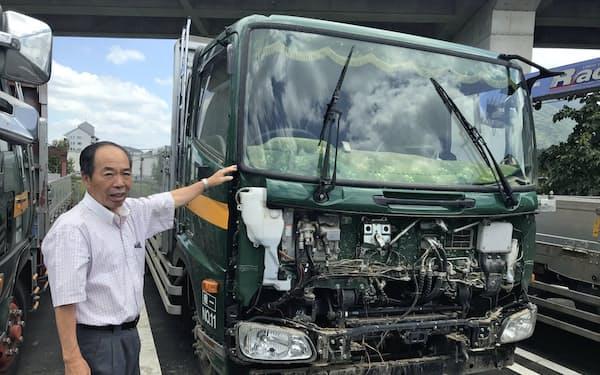 城戸運送の城戸猪喜夫社長と、浸水し廃車になったトラック(8月上旬、愛媛県大洲市)