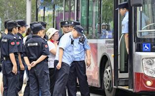 大規模な陳情活動が計画された政府機関の周辺で、警察官に取り囲まれる女性(6日、北京)=共同