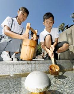長崎市の平和公園内の「平和の泉」から、献水用の水をくむ中学2年の増浦華さん(写真(左))ら(8日午前)=共同