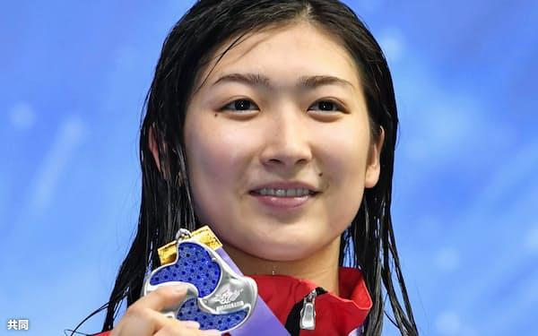 女子200メートル自由形で日本新記録をマークし2位に入り、表彰台で笑顔の池江璃花子(9日、東京辰巳国際水泳場)=共同