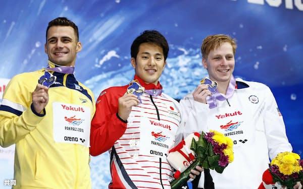 男子200メートルバタフライで2連覇を果たし、表彰式で笑顔の瀬戸大也=中央(10日、東京辰巳国際水泳場)=共同