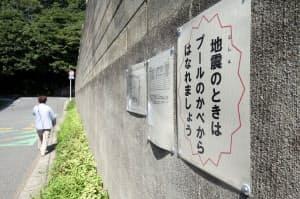 注意を促す紙が貼られた千葉市立幕張東小学校のプールのブロック塀(10日午後、千葉市花見川区)