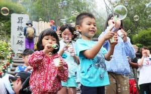 犠牲者の冥福と空の安全を祈り、シャボン玉を飛ばす子供たち(12日午前、群馬県上野村)