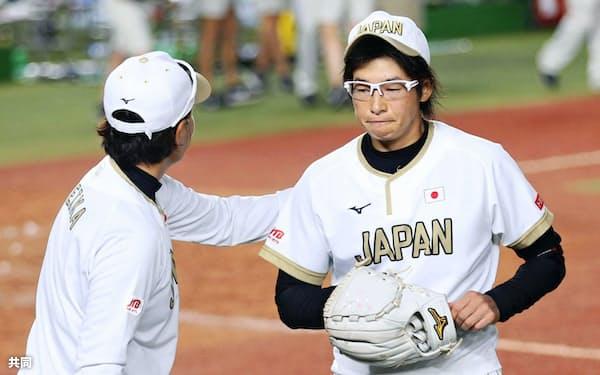 米国に逆転サヨナラ負けし、宇津木監督(左)に迎えられる上野=共同