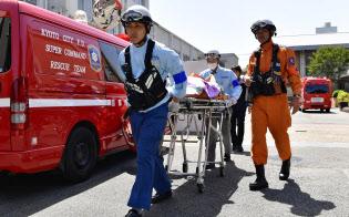 熱中症とみられる症状で倒れた生徒を搬送する救急隊員ら(5月、京都市南区)=共同
