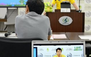 さいたま市の清水勇人市長(奥)の発言内容が表示された中継画面(さいたま市役所)=共同