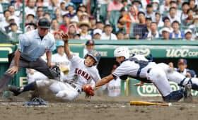 五回裏の2死二塁、興南・塚本の中前打で根路銘が本塁を狙うがタッチアウト=共同