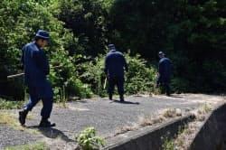 藤本理稀ちゃんが行方不明となった現場周辺を調べる警察官ら(13日、山口県周防大島町)=共同