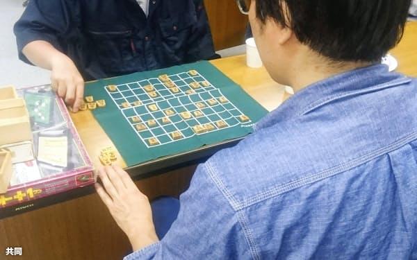 ひきこもりの人が集う居場所「よりどころ」でスタッフと将棋をする男性(手前、7月、札幌市)=共同