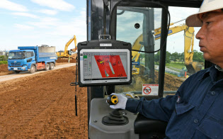 堤防工事でGPSを使い、踏み固めた位置と回数を確認する作業員(6月、さいたま市桜区)