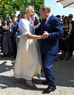 オーストリア外相(左)とダンスするプーチン氏(18日、オーストリア)=ロイター