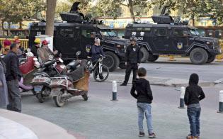 新疆ウイグル自治区にはイスラム教徒を強制的に収容する「再教育キャンプ」があるとされる(警察の装甲車両を見つめる同地区の住民ら、2017年11月5日)=AP