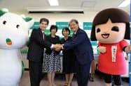 調印式後に握手する関係者ら(21日、静岡市)