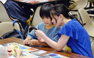 カードゲームで金融の仕組みを学ぶ親子(8日、東証)