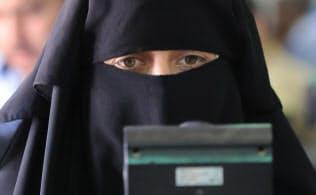 食料品スーパーのレジでレンズを見る女性(アズラック難民キャンプ)