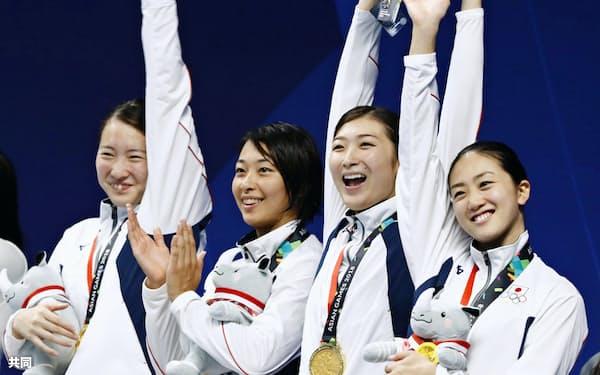 女子400メートルメドレーリレーで優勝し、表彰台で喜ぶ(左から)酒井、鈴木、池江、青木智(23日、ジャカルタ)=共同