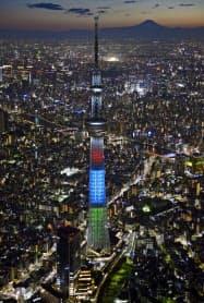 2020年東京パラリンピックまで2年となり、シンボルカラーにライトアップされた東京スカイツリー(25日夜、東京都内)=共同