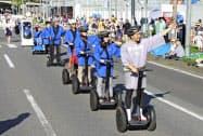 茨城県つくば市の中心部をパレードする移動支援ロボットの列。先頭は五十嵐立青市長(25日午後)=共同