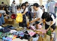 盛岡市の古着販売会社が開いた無料のフリーマーケットで服を選ぶ人たち(25日、広島県三原市)