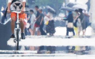 暑さで路面に現れた逃げ水(3日、東京都千代田区)