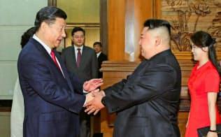 習近平氏の訪朝は見送りとなった(6月20日、北京で会談する金正恩氏と習近平国家主席(左)。コリアメディア提供・共同)