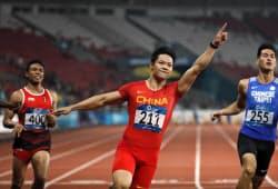 100メートル決勝で優勝した中国の蘇(中)=ロイター