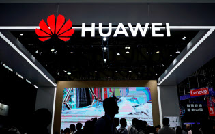 People walk past a sign board of Huawei at CES (Consumer Electronics Show) Asia 2018 in Shanghai, China June 14, 2018. REUTERS/Aly Song - RC13100DEAD0