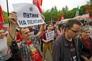 7月、モスクワで、ロシア政府の年金改革案に反発し、プーチン大統領に引退を促すメッセージを掲げる市民ら=ロイター