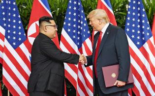 米朝首脳会談で共同声明に署名後、握手する北朝鮮の金正恩朝鮮労働党委員長(左)とトランプ米大統領(6月12日、シンガポール)=ロイター