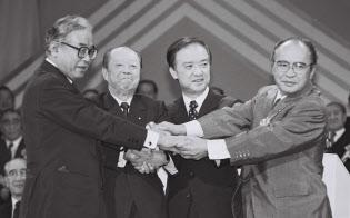 自民党臨時総会で握手する宮沢新総裁(左から2人目)=1991年10月、東京都千代田区の日比谷公会堂