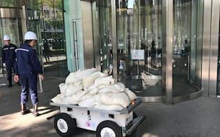 ゲリラ豪雨に備え、追尾運転機能を持つロボットで土のうを運ぶ(31日、東京・丸の内)