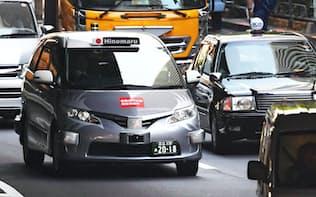 実証実験で公道を走行する自動運転タクシー(左)(27日午前、東京都港区)