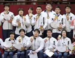 混合団体で優勝し金メダルを手に笑顔の日本チーム(1日、ジャカルタ)=共同