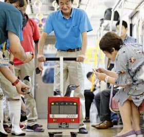 「京急油壺マリンパーク」の開業50周年イベントで、電車内を移動するペンギン(2日、京急電鉄品川―三浦海岸間)=共同