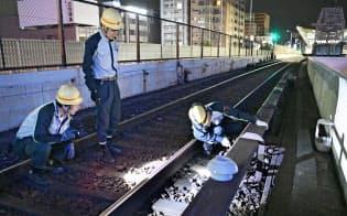 大阪メトロ御堂筋線の線路にある部品を交換する職員(8月31日、大阪市淀川区)