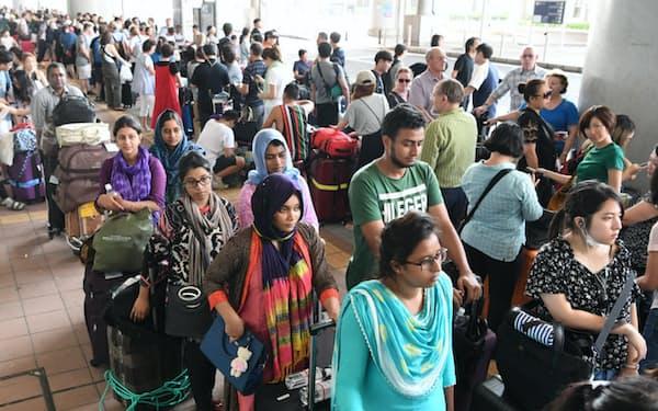 臨時バス乗り場に並ぶ外国人利用客(5日午後、関西空港)