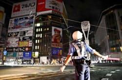 停電で信号が消えた札幌市中心部のすすきの交差点で、交通整理に当たる警察官(6日午前3時48分)=共同