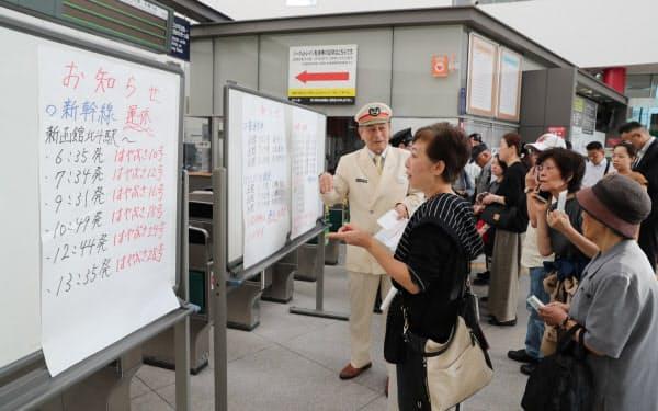 地震の影響で列車が運休し、駅員に問い合わせる利用者(6日午前、北海道函館市のJR函館駅)