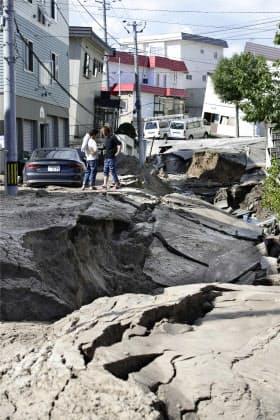 地震により陥没した道路と傾いた建物(6日午前、札幌市清田区))=共同