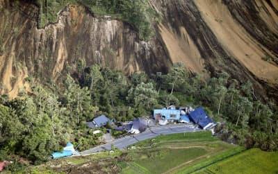 地震による土砂崩れで倒壊した家屋(6日午前、北海道厚真町)=共同
