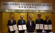 M&Aの協定を結んだ山形銀行の長谷川吉茂頭取(中)と県内4信金理事長(6日、山形市)