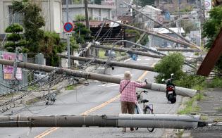 台風の強風で倒れ、道路をふさぐ電柱(6日、大阪府泉南市)