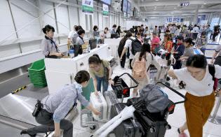 運航を再開した国際線の搭乗手続きをする訪日客ら(8日午前、関西空港)