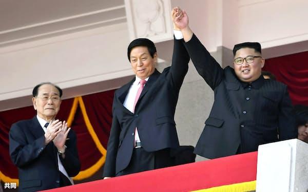 北朝鮮の建国70年を祝う軍事パレードで、中国の栗戦書・全人代常務委員長(中央)と手を上げて歓声に応える金正恩朝鮮労働党委員長。左は金永南最高人民会議常任委員長=9日、平壌の金日成広場(共同)
