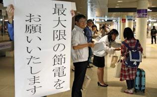 札幌市の地下歩道に立ち、節電を呼び掛ける北海道電力の社員ら(9日午後)=共同