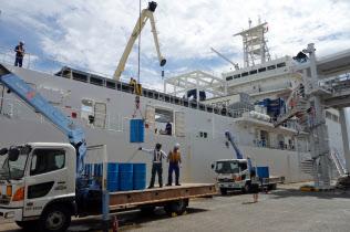 通信設備を動作させる燃料が入ったドラム缶を海底ケーブルの敷設船「きずな」に積み込む(10日午前、横浜市)