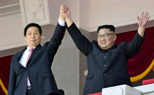 9月9日、平壌での軍事パレードで、中国の栗戦書・全人代常務委員長(左)の手を高く掲げる金正恩委員長=共同